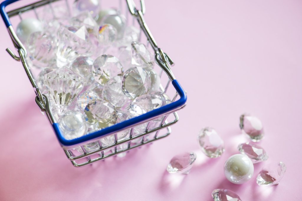 mini shopping cart with diamonds on a pink background
